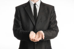 Businessman and gesture topic: a man in a black suit with a tie folded his hands in front of him isolated on a white background in Stock Photography