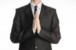 Businessman and gesture topic: a man in a black suit with a tie folded his hands in front of him and praying, meditating businessm Royalty Free Stock Images