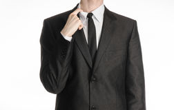 Businessman and gesture topic: a man in a black suit and tie holding a hand to his shirt collar isolated on a white background in Royalty Free Stock Images