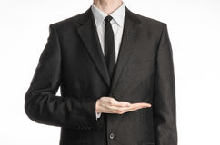 Businessman and gesture topic: a man in a black suit and tie holding his hand in front of him isolated on a white background in st Royalty Free Stock Image