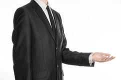 Businessman and gesture topic: a man in a black suit and tie holding his hand in front of him isolated on a white background in st Stock Image
