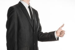 Businessman and gesture topic: a man in a black suit and tie holding his hand in front of him and shows thumb up isolated on white. Background royalty free stock photo