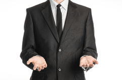Businessman and gesture topic: a man in a black suit and tie holding two hands in front isolated on white background in studio Royalty Free Stock Image
