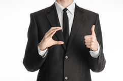 Businessman and gesture topic: a man in a black suit and tie holds his right hand and the left shows a thumb-up sign isolated on w Stock Photos
