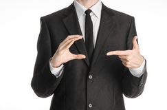 Businessman and gesture topic: a man in a black suit and tie holds his right hand and pointing to her left isolated on white backg Royalty Free Stock Photography