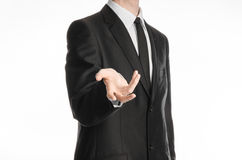 Businessman and gesture topic: a man in a black suit and tie holds out his hand isolated on a white background in studio Stock Image