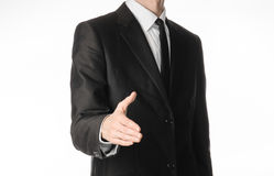 Businessman and gesture topic: a man in a black suit and tie holds out his hand to greet isolated on white background in studio Royalty Free Stock Image