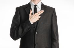 Businessman and gesture topic: a man in a black suit with a tie put his hand on his chest with a gesture in the form of a pistol i Stock Photos
