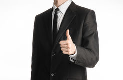 Businessman and gesture topic: a man in a black suit with a tie showing hand gesture thumbs up isolated on white background in stu Royalty Free Stock Photo