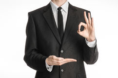 Businessman and gesture topic: a man in a black suit with a tie showing okay sign with his left hand and holds his right hand on a Royalty Free Stock Photo