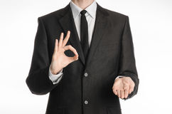 Businessman and gesture topic: a man in a black suit with a tie showing okay sign with his left hand and holds his right hand on a Royalty Free Stock Photography