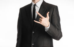 Businessman and gesture topic: a man in a black suit with a tie showing rock hand gesture on an isolated white background in studi Royalty Free Stock Photography