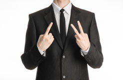 Businessman and gesture topic: a man in a black suit with a tie showing a sign with his right hand and the left hand sign two on t Royalty Free Stock Photos