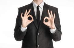 Businessman and gesture topic: a man in a black suit with a tie showing two hands sign of okay isolated on white background in stu Stock Photography