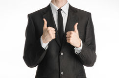 Businessman and gesture topic: a man in a black suit with a tie showing two hands thumbs up isolated on white background in studio Stock Photos