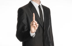 Businessman and gesture topic: a man in a black suit with a tie shows an index finger upward on white isolated background in studi Royalty Free Stock Images