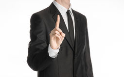 Businessman and gesture topic: a man in a black suit with a tie shows an index finger upward on white isolated background in studi Stock Images