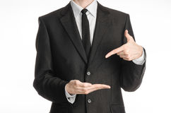 Businessman and gesture topic: a man in a black suit with a tie shows the left hand index finger on his right hand on a white isol Royalty Free Stock Photo