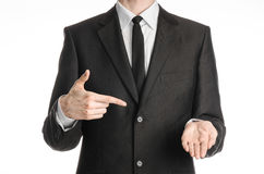 Businessman and gesture topic: a man in a black suit with a tie shows the right hand index finger on his left hand on an isolated Stock Photography