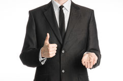Businessman and gesture topic: a man in a black suit with a tie shows the right hand thumb up and holding his left hand on an isol. Ated white background Royalty Free Stock Image