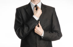 Businessman and gesture topic: a man in a black suit with a tie straightens his tie isolated on white background in studio Stock Image