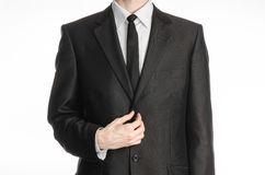 Businessman and gesture topic: a man in a black suit with a tie straightens his tie isolated on white background in studio Royalty Free Stock Photo