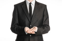 Businessman and gesture topic: a man in a black suit and tie two hands clasped in front of him isolated on a white background in s Royalty Free Stock Images