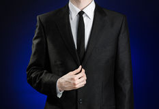 Businessman and gesture topic: a man in a black suit and white shirt correcting a jacket and tie on a dark blue background in stud Stock Images
