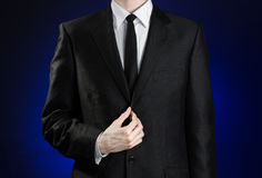 Businessman and gesture topic: a man in a black suit and white shirt correcting a jacket and tie on a dark blue background in stud Stock Image