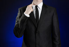 Businessman and gesture topic: a man in a black suit and white shirt correcting a jacket and tie on a dark blue background in stud Stock Photography