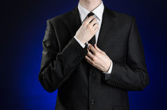 Businessman and gesture topic: a man in a black suit and white shirt correcting a jacket and tie on a dark blue background in stud Royalty Free Stock Photography