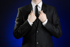 Businessman and gesture topic: a man in a black suit and white shirt correcting a jacket and tie on a dark blue background in stud Royalty Free Stock Image