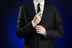 Businessman and gesture topic: a man in a black suit and white shirt correcting a jacket and tie on a dark blue background in stud Royalty Free Stock Photo