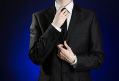 Businessman and gesture topic: a man in a black suit and white shirt correcting a jacket and tie on a dark blue background in stud Royalty Free Stock Photos