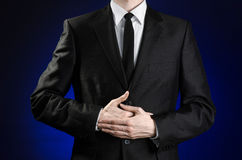 Businessman and gesture topic: a man in a black suit and a white shirt holding hands on the sick belly on a dark blue background i Royalty Free Stock Photo