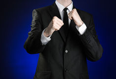 Businessman and gesture topic: a man in a black suit and white shirt holding his fists in front of him on a dark blue background i. N studio Stock Photo