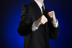 Businessman and gesture topic: a man in a black suit and white shirt holding his fists in front of him on a dark blue background i Royalty Free Stock Photos