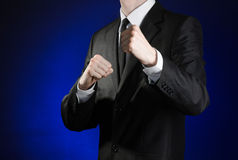 Businessman and gesture topic: a man in a black suit and white shirt holding his fists in front of him on a dark blue background i Stock Image