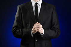 Businessman and gesture topic: a man in a black suit and white shirt holds her hands together in front of you and prays, meditates. On a dark blue background in Royalty Free Stock Image