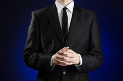 Businessman and gesture topic: a man in a black suit and white shirt holds her hands together in front of you and prays, meditates. On a dark blue background in Stock Photo