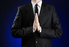 Businessman and gesture topic: a man in a black suit and white shirt holds her hands together in front of you and prays, meditates. On a dark blue background in Stock Photos