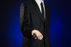 Businessman and gesture topic: a man in a black suit and white shirt holds up a hand against the dark blue isolated background in Royalty Free Stock Images