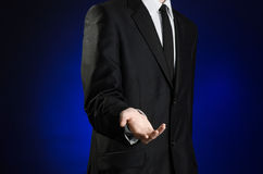 Businessman and gesture topic: a man in a black suit and white shirt holds up a hand against the dark blue isolated background in Stock Photography