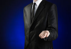 Businessman and gesture topic: a man in a black suit and white shirt holds up a hand against the dark blue isolated background in Royalty Free Stock Photo