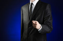 Businessman and gesture topic: a man in a black suit and white shirt showing fig hand on a dark blue background in studio isolated. Businessman and gesture topic Royalty Free Stock Images