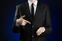 Businessman and gesture topic: a man in a black suit and white shirt showing gestures with hands on a dark blue background in stud Royalty Free Stock Photos
