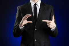 Businessman and gesture topic: a man in a black suit and white shirt showing gestures with hands on a dark blue background in stud Stock Image