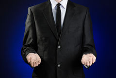 Businessman and gesture topic: a man in a black suit and white shirt showing gestures with hands on a dark blue background in stud Stock Photos