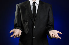 Businessman and gesture topic: a man in a black suit and white shirt showing gestures with hands on a dark blue background in stud. Io stock images