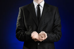 Businessman and gesture topic: a man in a black suit and white shirt showing gestures with hands on a dark blue background in stud Stock Photo